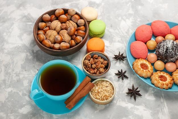 Vista dall'alto deliziose torte con macarons noci tè e biscotti sulla superficie bianca