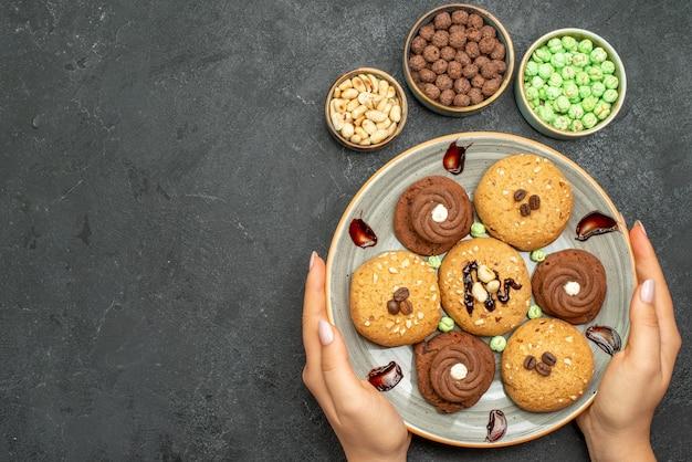 Vista dall'alto deliziose caramelle con piccoli biscotti su uno spazio buio