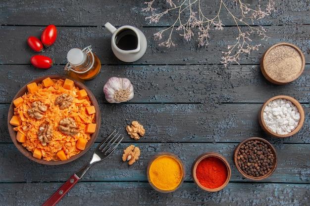 ダークブルーのデスクナッツダイエットサラダの色の健康にクルミと調味料を添えたトップビューのおいしいニンジンサラダ