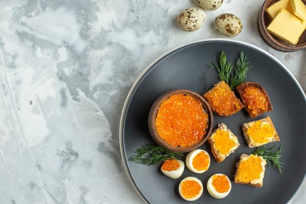 Вид сверху вкусные бутерброды с икрой с вареными яйцами внутри тарелка белый фон завтрак обед рыба обед тосты хлеб еда