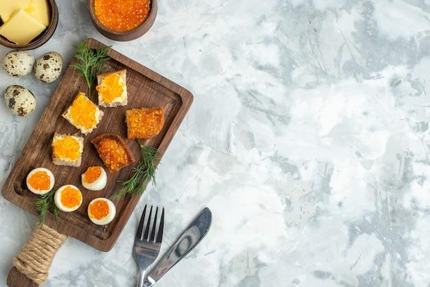Вид сверху вкусные бутерброды с икрой с вареными яйцами на разделочной доске белая поверхность завтрак морепродукты обед еда горизонтальная тостовая мука рыба