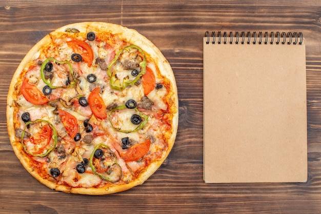 Vista dall'alto deliziosa pizza al formaggio su una superficie di legno marrone
