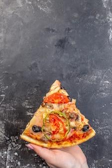 Вид сверху вкусной сырной пиццы, нарезанной и поданной в женской руке на серой поверхности