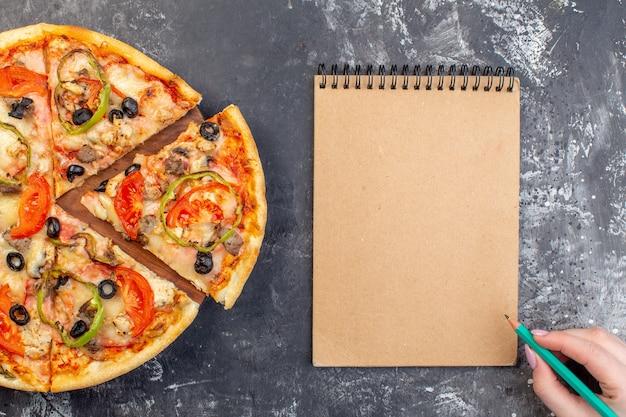 Vista dall'alto deliziosa pizza al formaggio affettata e servita su una superficie grigia
