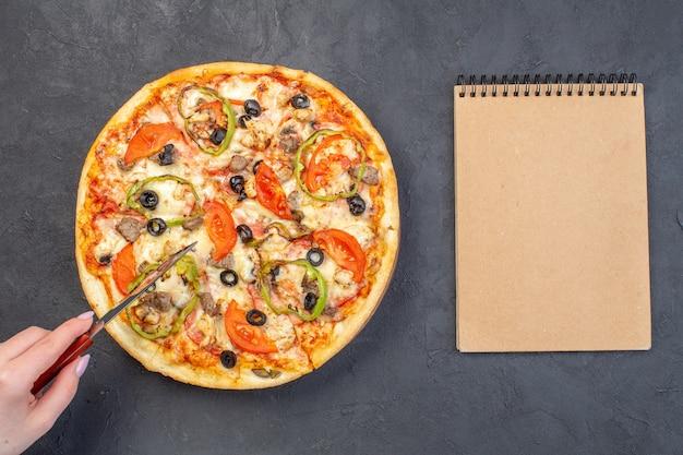 暗い表面にオリーブペッパーとトマトを添えたトップビューのおいしいチーズピザ