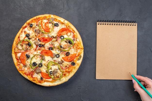 Vista dall'alto una deliziosa pizza al formaggio con olive, pepe e pomodori sulla superficie scura