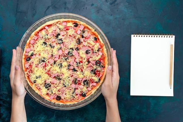 밝은 파란색 책상에 유리 팬 안에 올리브 토마토 소스 소시지와 상위 뷰 맛있는 치즈 피자.