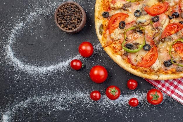 Vista dall'alto una deliziosa pizza al formaggio con pomodori rossi su sfondo scuro