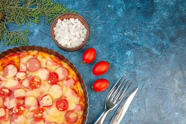 Vista dall'alto deliziosa pizza al formaggio con salsicce e pomodori sullo sfondo blu torta di pasta alimentare foto a colori fast-food italiano