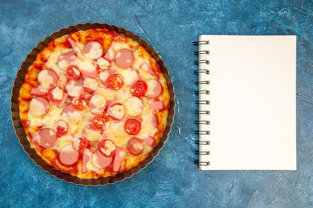 Top view delicious cheese pizza with sausages and tomatoes on blue background salad food cake color photo fast-food