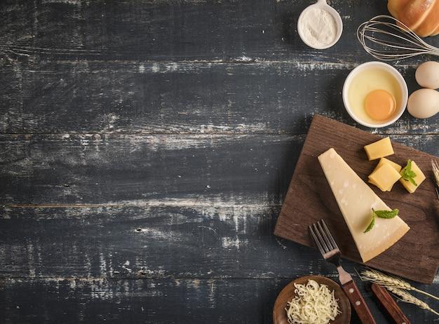 Vista dall'alto di un delizioso piatto di formaggi con noci, uova e farina su un tavolo con spazio di copia