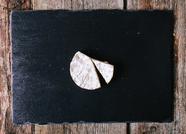 Top view of delicious cheese on slate board