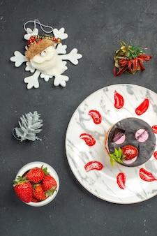 Вид сверху вкусного чизкейка с клубникой и шоколадом на овальной тарелке с клубничными рождественскими игрушками на темном фоне