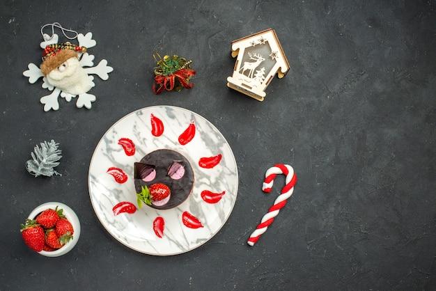 暗い背景の上のイチゴのクリスマスのおもちゃの楕円形のプレートボウルにイチゴとチョコレートのトップビューおいしいチーズケーキ