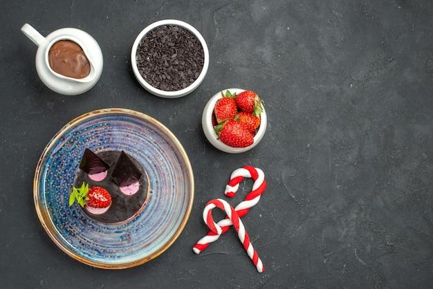 暗い孤立した背景にイチゴチョコレートクリスマスキャンディーと楕円形のプレートボウルにイチゴとチョコレートのトップビューおいしいチーズケーキ