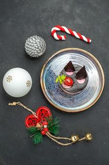 暗い孤立した背景の上の楕円形のプレートのクリスマスツリーのおもちゃにイチゴとチョコレートのトップビューおいしいチーズケーキ