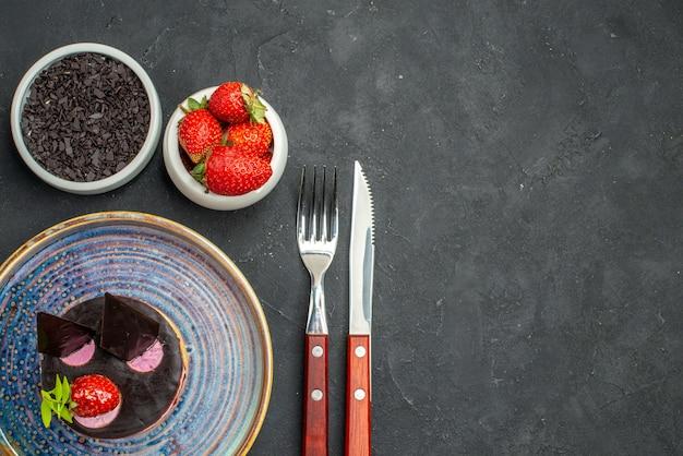 トップビュー暗い孤立した背景にイチゴチョコレートフォークとナイフとプレートボウルにイチゴとチョコレートとおいしいチーズケーキ