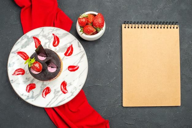 トップビューイチゴとチョコレートのおいしいチーズケーキプレートに赤いショールボウルイチゴと暗い孤立した背景のノートブック