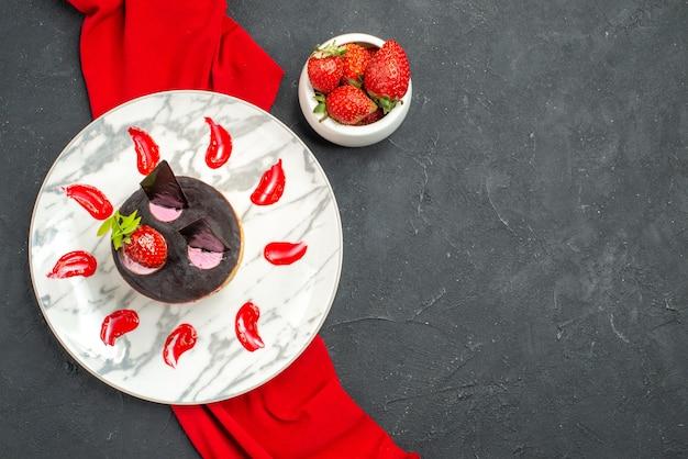 Вид сверху вкусный чизкейк с клубникой и шоколадом на тарелке, миска из красной шали с клубникой на темном изолированном фоне