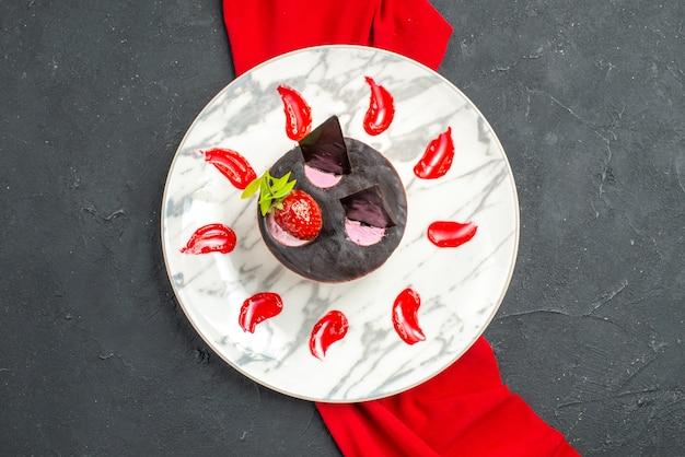 暗い孤立した背景の上のプレート赤いショールにイチゴとチョコレートのトップビューおいしいチーズケーキ