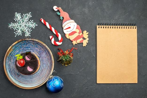 크리스마스 접시에 딸기와 초콜릿을 곁들인 맛있는 치즈 케이크는 어두운 격리된 배경에 있는 노트북을 자세히 설명합니다.