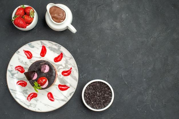 Vista dall'alto deliziosa cheesecake con fragole e cioccolato su piatto ovale ciotola di fragole e cioccolato su sfondo scuro isolato