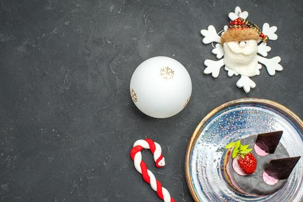 Vista dall'alto deliziosa cheesecake con fragole e cioccolato su giocattoli di natale piatto ovale su sfondo scuro isolato