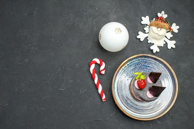 Vista dall'alto deliziosa torta di formaggio con fragole e cioccolato su piatto ovale albero di natale giocattoli su sfondo scuro isolato