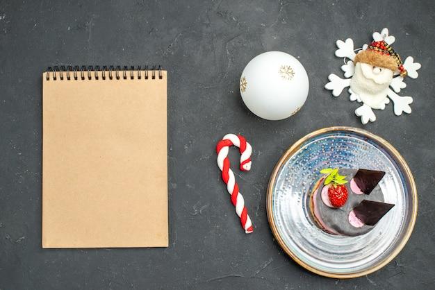 Vista dall'alto deliziosa cheesecake con fragole e cioccolato su piatto ovale albero di natale gioca con un quaderno su sfondo scuro isolato