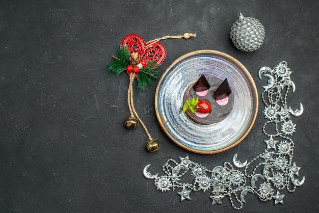Vista dall'alto deliziosa cheesecake con fragole e cioccolato su ornamenti di natale ovali in argento su sfondo scuro isolato