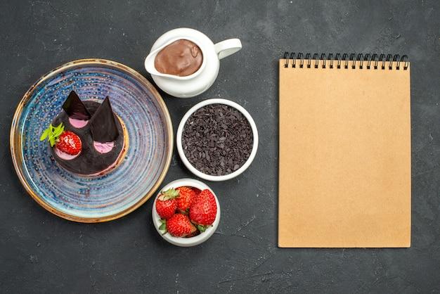 Vista dall'alto deliziosa cheesecake con fragole e cioccolato su ciotole con fragole al cioccolato su sfondo scuro isolato