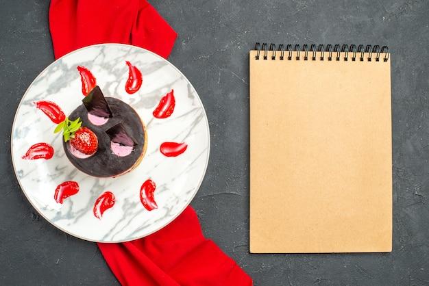 Vista dall'alto deliziosa cheesecake con fragole e cioccolato su piatto scialle rosso un quaderno su sfondo scuro isolato