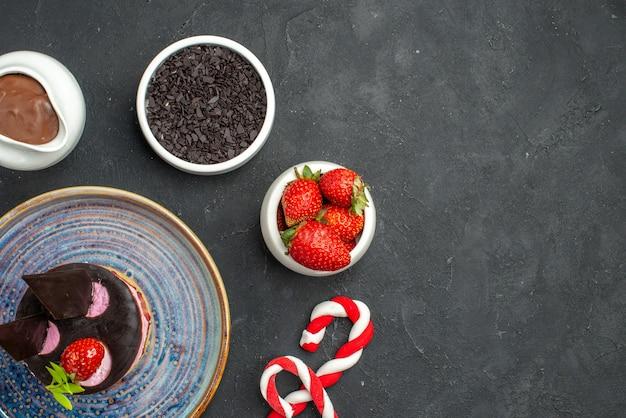 暗い孤立した背景にイチゴと楕円形のプレートボウルにイチゴとおいしいチーズケーキの上面図