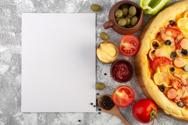 灰色の背景のファーストフードのイタリアの生地の食事にオリーブソーセージと赤いトマトのおいしい安っぽいピザのトップビュー