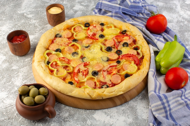 Вид сверху вкусной сырной пиццы с оливками, сосисками и помидорами на сером фоне фаст-фуд тесто еда еда
