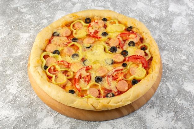 灰色の背景のファーストフードのイタリアの生地の食事の灰色の背景にオリーブソーセージとトマトのおいしい安っぽいピザのトップビュー