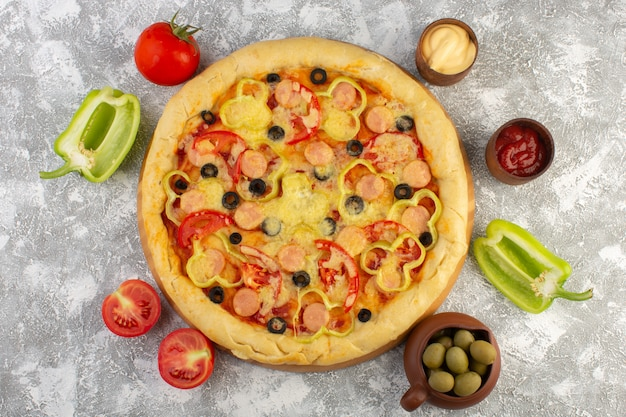 Вид сверху вкусной сырной пиццы с оливками, сосисками и помидорами на сером столе фаст-фуд итальянское тесто