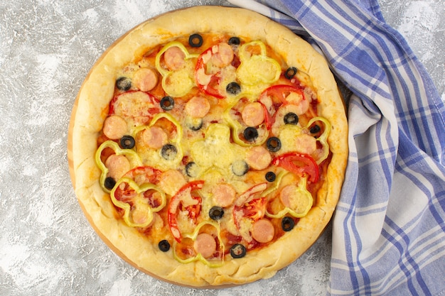 Top view delicious cheesy pizza with olives sausages and tomatoes on the grey background fast-food italian dough meal