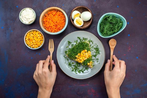 Vista dall'alto deliziosa insalata di pollo con semi di carote affettate uova sulla scrivania scura.