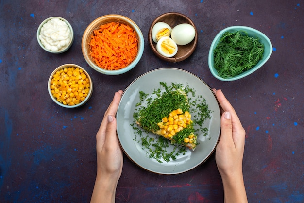 옥수수와 상위 뷰 맛있는 치킨 샐러드는 어두운 책상에 당근 계란을 슬라이스.