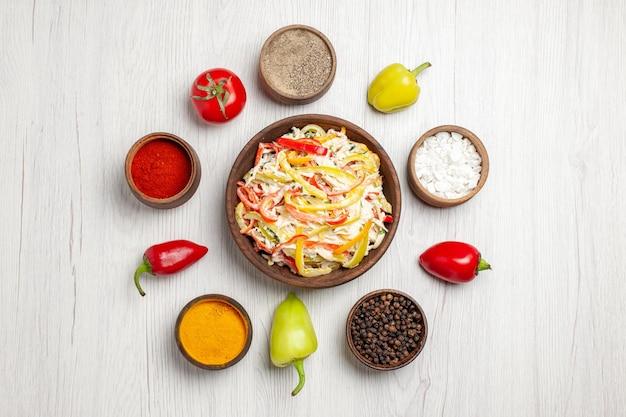 明るい白い机の上にさまざまな調味料を使ったおいしいチキンサラダの上面図スナック熟した食事肉の新鮮なサラダ
