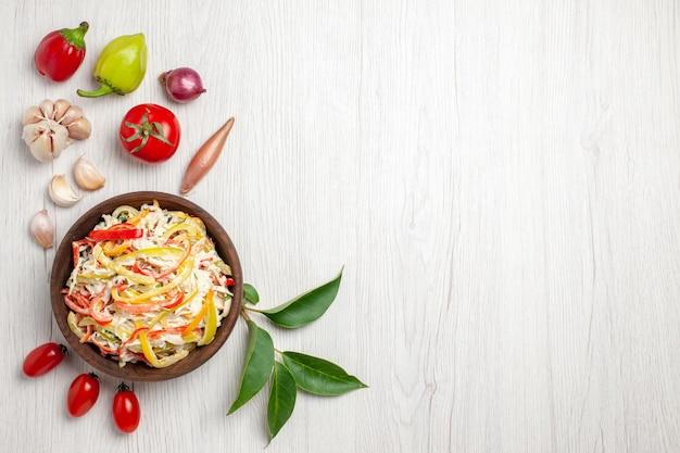 Vista dall'alto deliziosa insalata di pollo con maionese e verdure su spuntino da scrivania bianco insalata di farina di carne di colore maturo