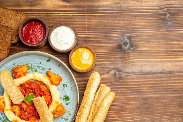 Вид сверху вкусные кусочки курицы с картофельным пюре и приправами на деревянном столе, еда из картофеля, острый перец