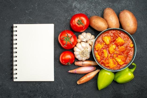 어두운 회색 배경 소스 접시 치킨 토마토 고기에 토마토 소스와 야채와 함께 상위 뷰 맛있는 치킨 조각
