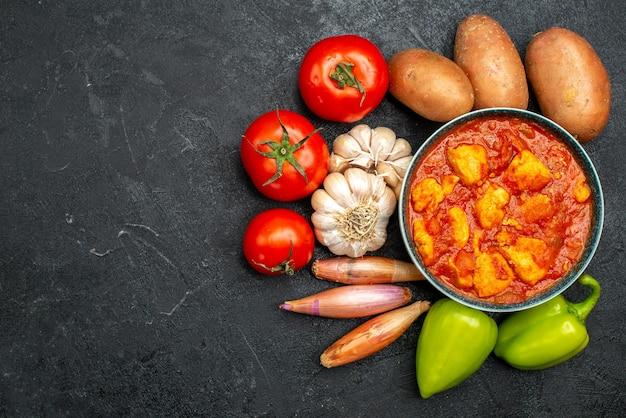 トップビューダークグレーの背景ソース皿にトマトソースと野菜を添えたおいしいチキンスライスチキントマト肉
