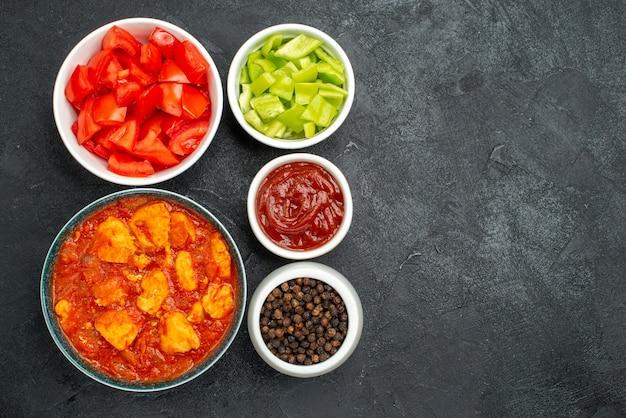 Vista dall'alto deliziose fette di pollo con salsa di pomodoro e verdure fresche su fondo scuro piatto di salsa di pollo carne di pomodoro