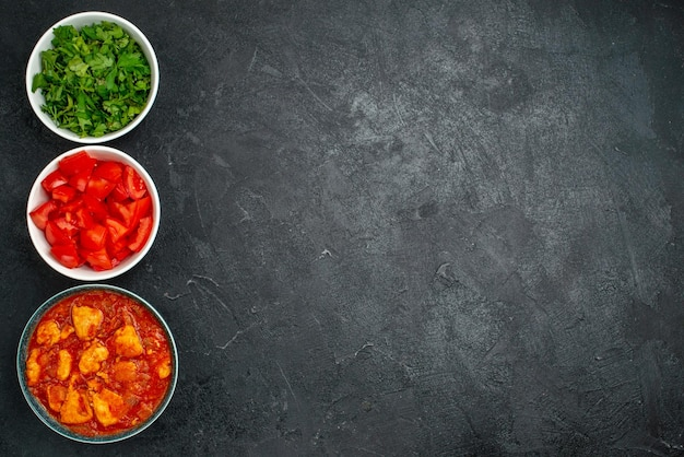 Top view delicious chicken slices with tomato sauce and greens on dark grey background sauce dish meat chicken tomato