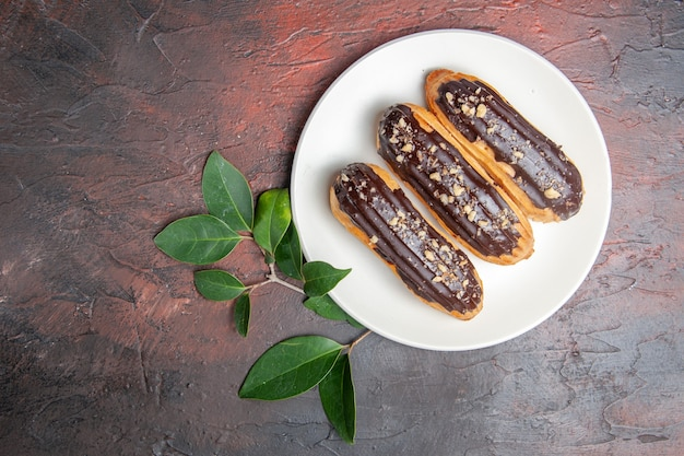 Top view delicious choco eclairs inside plate on dark table dessert sweet cake pie