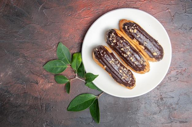 Вид сверху вкусные шоколадные эклеры внутри тарелки на темном столе, десерт, сладкий пирог