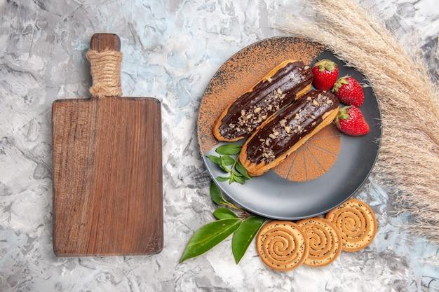 Vista dall'alto deliziosi bignè al cioccolato con biscotti su un dolce biscotto da tavola bianco chiaro